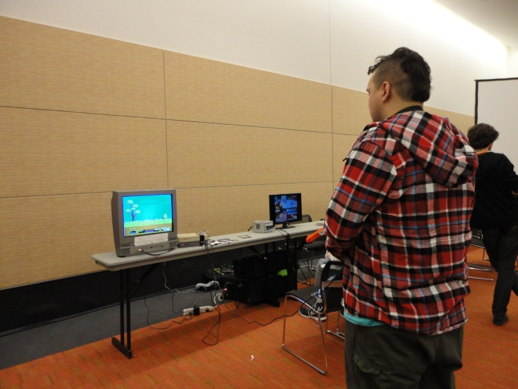 A room with old school consoles and video games to play, like this guy playing Duck Hunt.