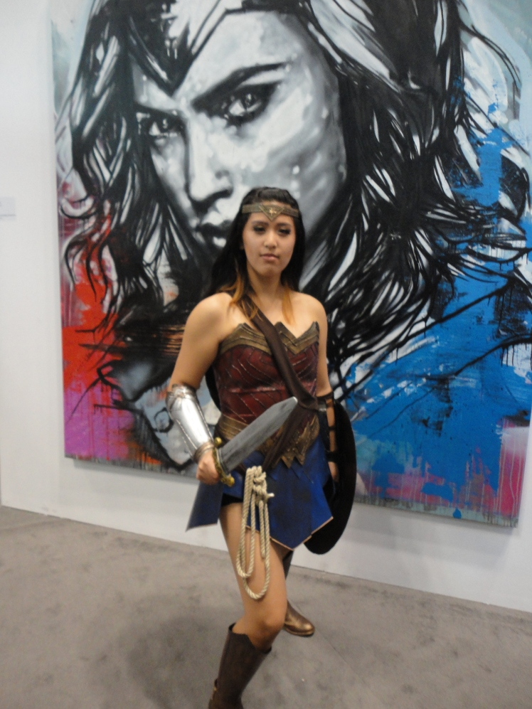 Wonder Woman herself posing in front of her portrait.